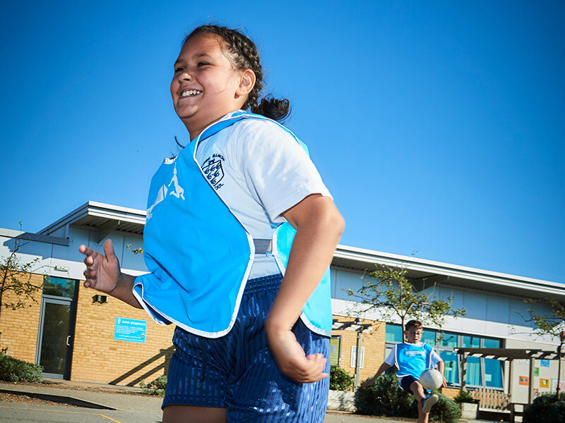 Girl wearing a blue vest running in playground