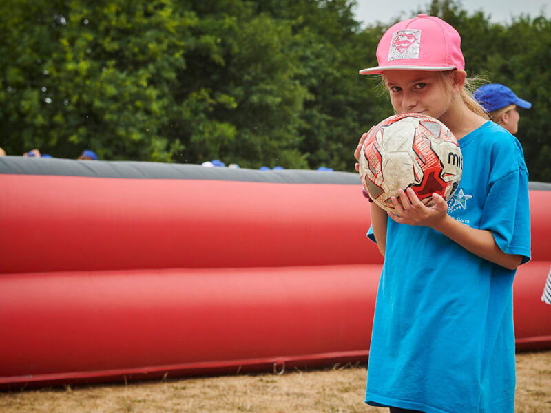 Girl wearing a pink cap holding a football